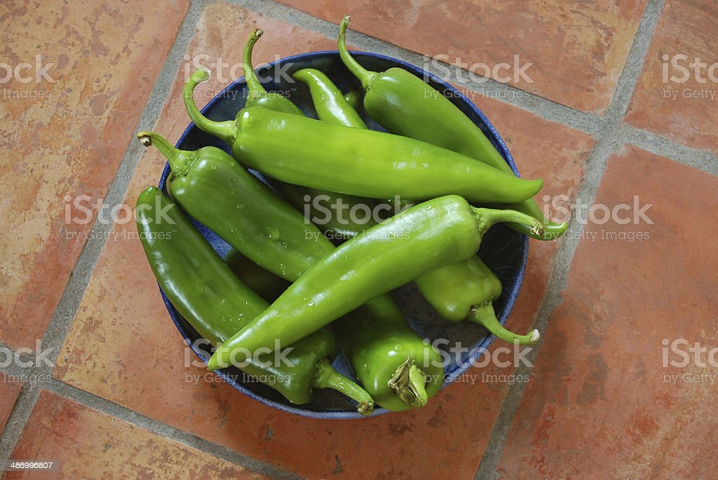 Fresh Green Chiles in Ceramic Bowl on Mexican Tiles stock photo