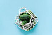istock Fresh green cucumbers vegetables in reusable shopping eco-frendly mesh bag on blue background. Concept no plastic and zero waste. Copy space Top view Flat lay 1167486308