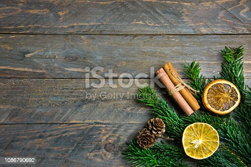 istock Fresh green fluffy bushy fir tree branches cinnamon dried orange slices pine cones on old plank wood background. Christmas New Year greeting card poster with copy space. Retro vintage style 1086790692