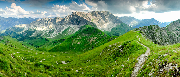 istock Fresh green grass meadow and mountains slopes. Summer or springtime. 925288340