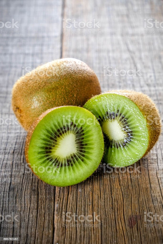 Fresh green healthy kiwi fruits and sliced on wooden table background royalty free stockfoto