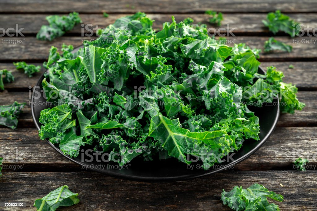 Fresh green healthy superfood vegetable kale leaves in a black plate on wooden rustic table stock photo
