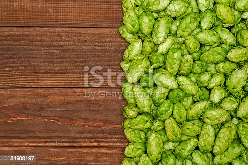 istock Fresh green hops on a wooden background. Ingredient for beer production. Top view with copy space 1184908197