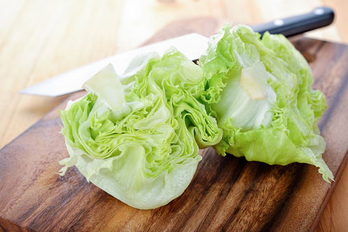 istock fresh green iceberg lettuce on cutting board 696841494