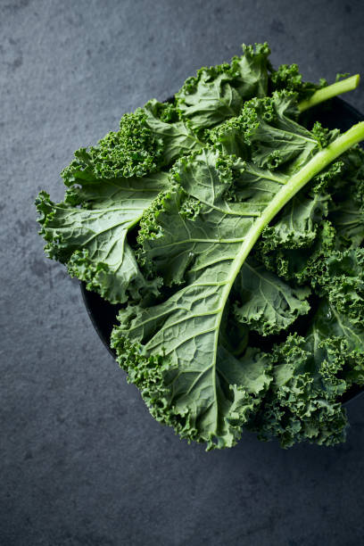 Fresh green kale leaves in a bowl on dark stone background. Healthy food ingredients stock photo