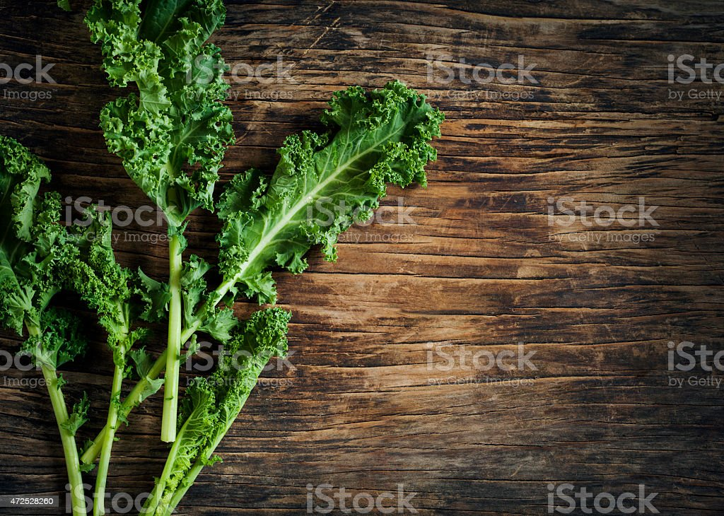 Fresh Green Kale on wooden background stock photo