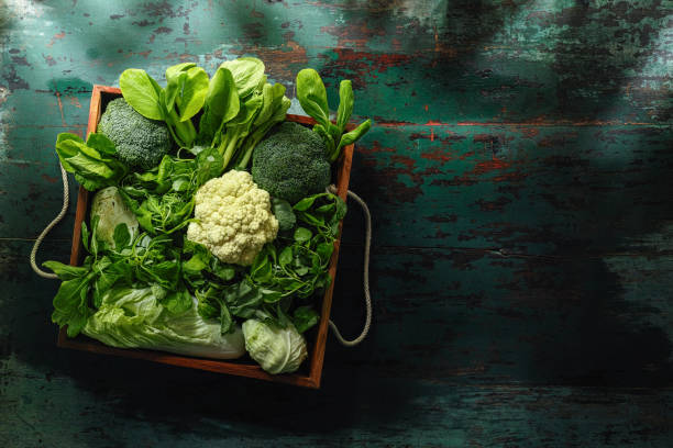 Fresh green leaf vegetables in an old wooden crate on an old wooden turquoise table. stock photo