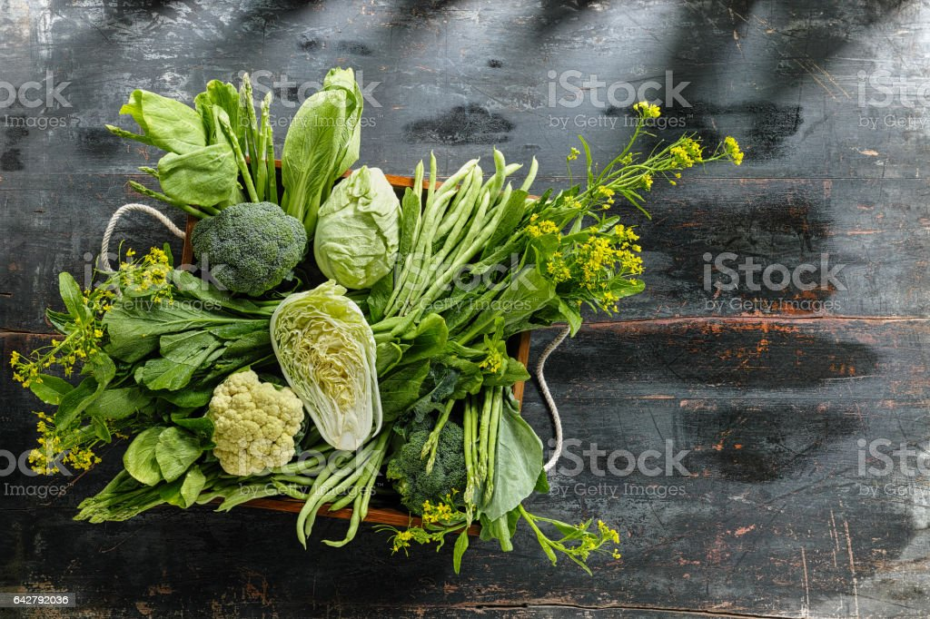 Fresh green leaf vegetables in an old wooden crate on an old wooden table. stock photo