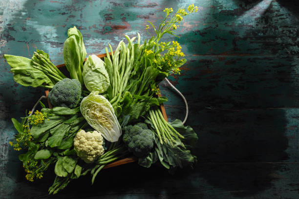 Fresh green leaf vegetables in an old wooden crate on an old wooden turquoise table. - foto stock
