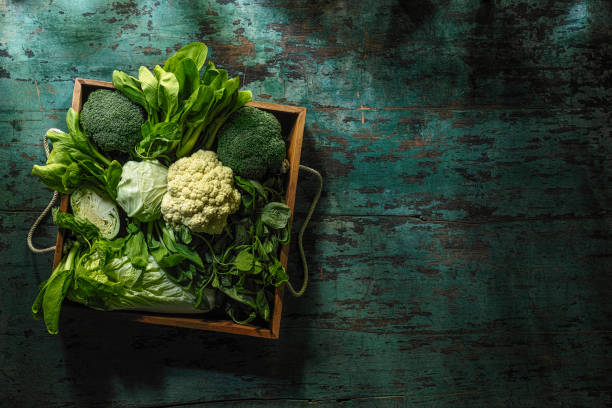 świeże zielone warzywa liściowe w starej drewnianej skrzyni na starym drewnianym turkusowym stole. - kapustowate zdjęcia i obrazy z banku zdjęć