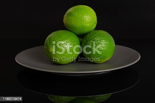 istock Fresh green lime isolated on black glass 1165213474