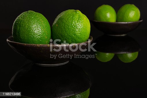 istock Fresh green lime isolated on black glass 1165213495