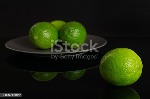 istock Fresh green lime isolated on black glass 1165213522