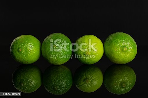 istock Fresh green lime isolated on black glass 1165213524