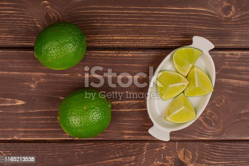 istock Fresh green lime on brown wood 1165213538
