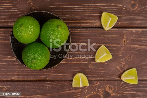 istock Fresh green lime on brown wood 1165213543