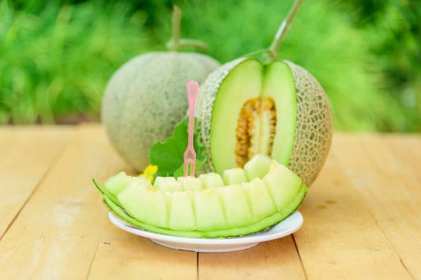Fresh green melon on wood plate stock photo