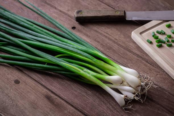 verse groene ui op houten tafel - bosui stockfoto's en -beelden