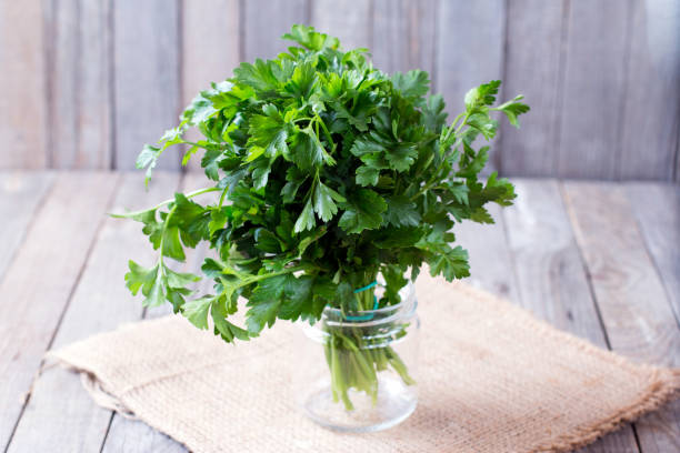 fresh green parsley on the wooden table - parsley stock photos and pictures