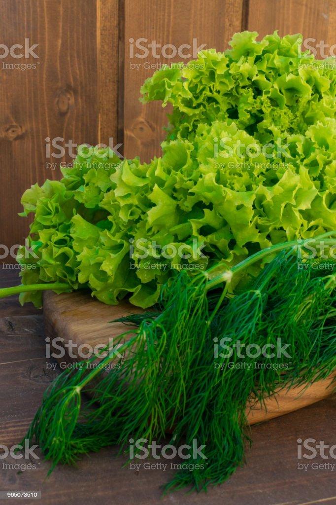 fresh green salad and dill on wood background zbiór zdjęć royalty-free