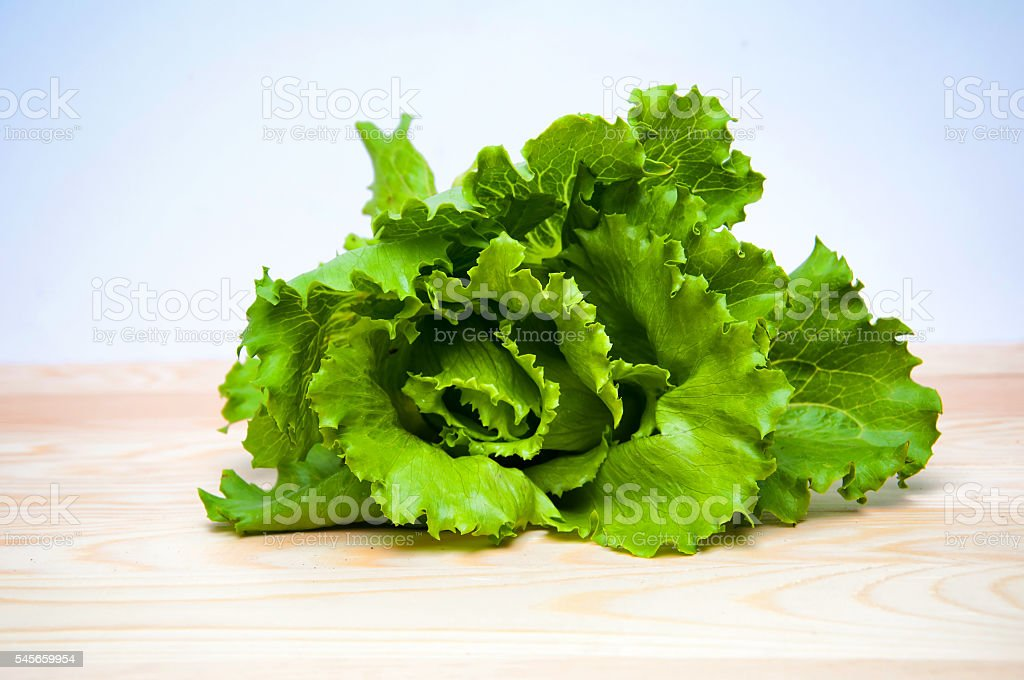 Fresh green salad on wooden table - Photo