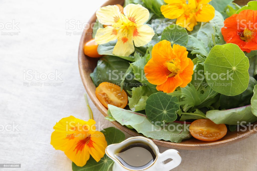 Fresh green salad with edible flowers nasturtium in wooden serving dish stock photo