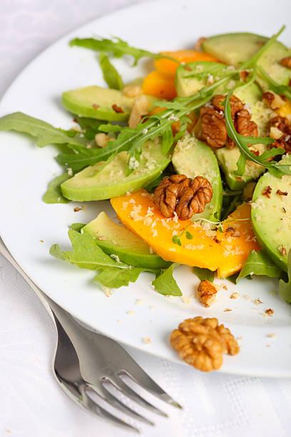 fresh green salad with mango, avocado, arugula and walnuts stock photo