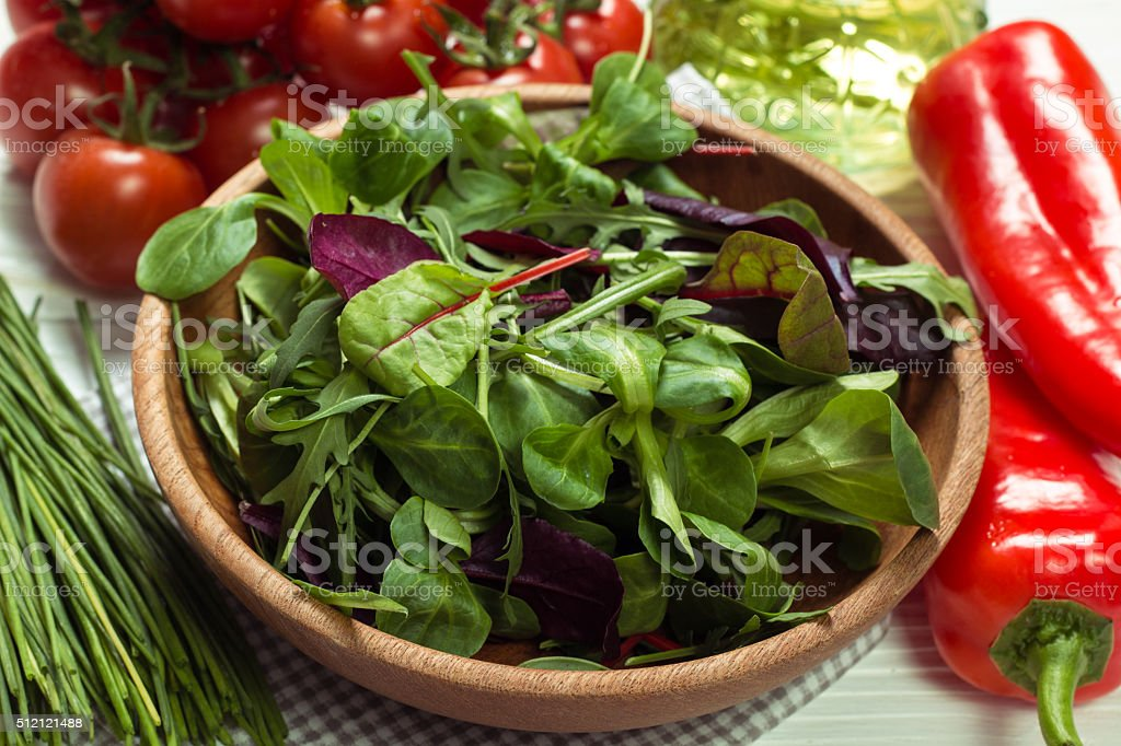 Fresh green salad with spinach ,ruccola,lettuce on wooden table. stock photo
