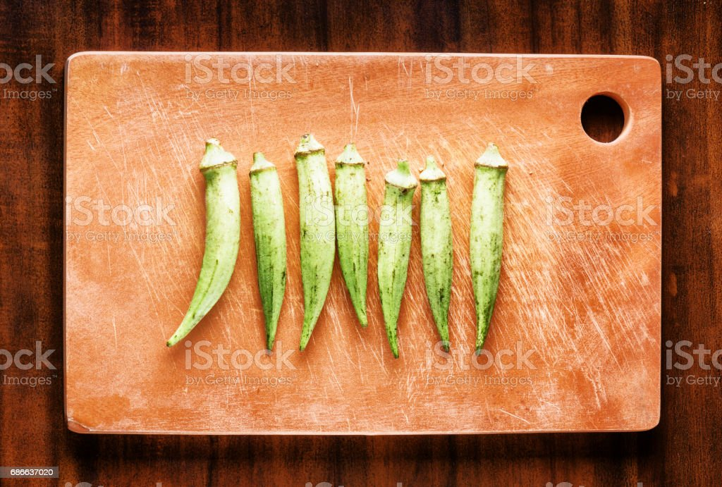 Fresh green seed pods okra on a wooden board. Healthy eco food royalty-free stock photo