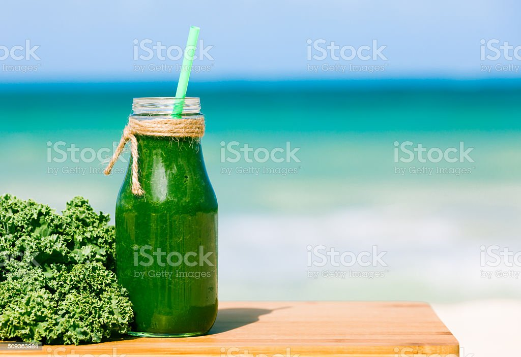 Fresh green smoothie on the beach stock photo