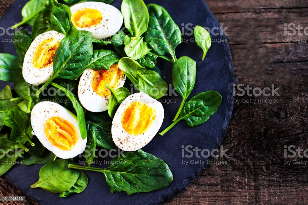 Fresh green spinach baby leaves and boiled eggs cut in a half on wooden background stock photo