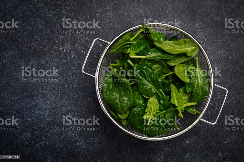 Fresh green spinach leaves on a dark concrete background. stock photo