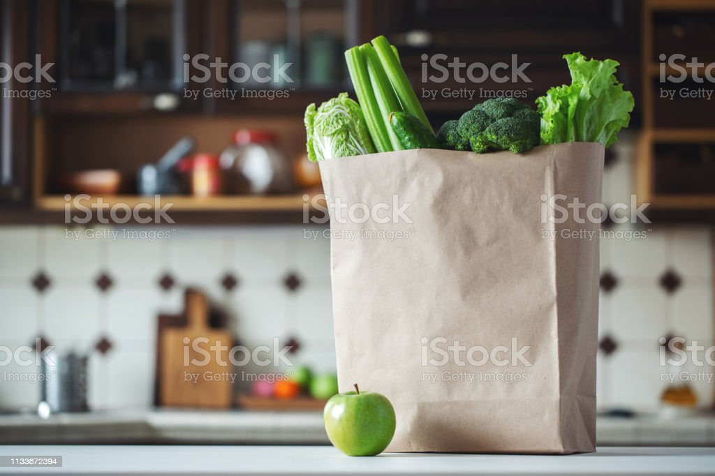 Fresh green vegetables and fruits in a paper bag. stock photo