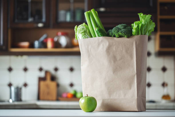 fresh green vegetables and fruits in a paper bag. - onion juice stock photos and pictures