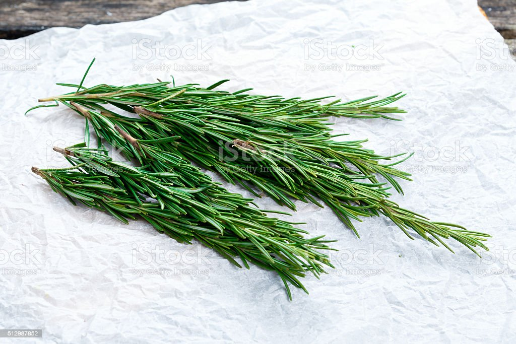Fresh Green Vegetables Bunch of Rosemary on crumpled paper stock photo