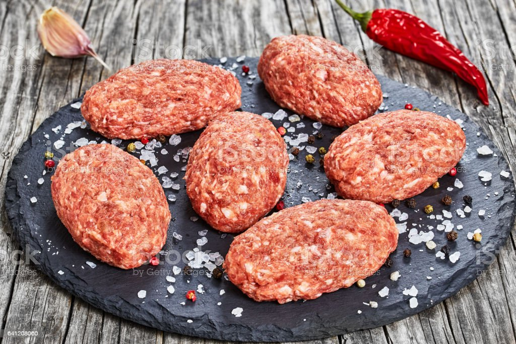 fresh ground raw meat cutlets on slate plate stock photo
