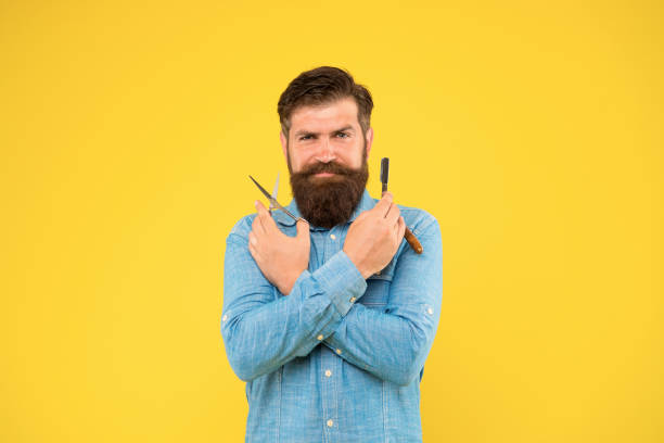Fresh hairstyle. Barbershop concept. Barbershop salon. Personal stylist. Vintage barber. Bearded man hold razor and scissors. Classic values. Retro barbershop. Hipster with tools. Designing haircut stock photo