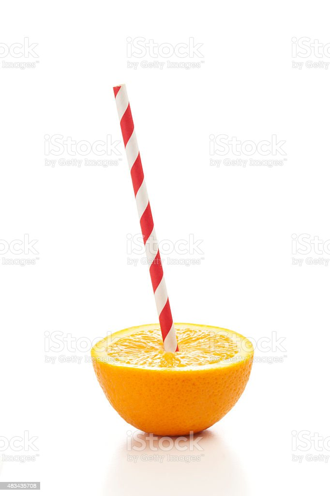 Fresh half orange with drinking straw on white background stock photo