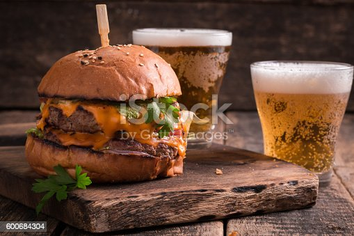 istock Fresh hamburger with a beer on a wooden table. 600684304
