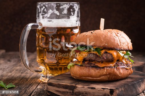 istock Fresh hamburger with a beer on a wooden table. 610747418