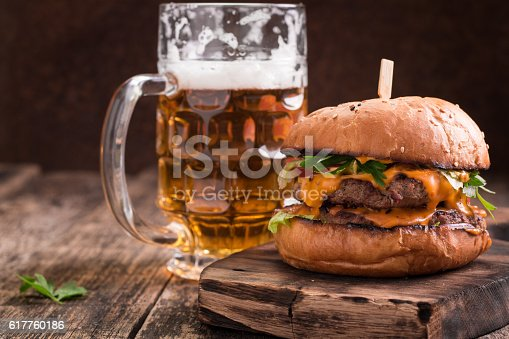 istock Fresh hamburger with a beer on a wooden table. 617760186