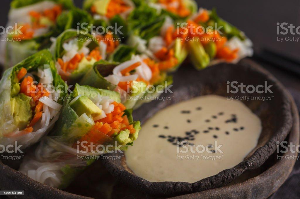 Fresh handmade vegan asian spring rolls with rice noodles, avocado, carrots and tahini dressing on black dish, dark background. stock photo