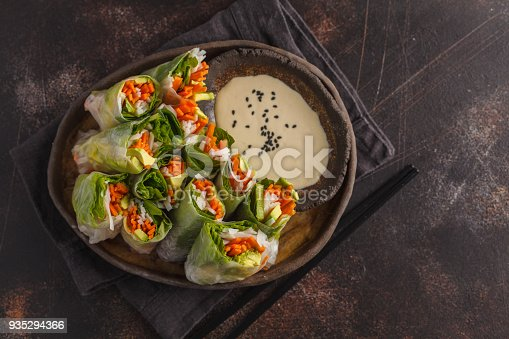 istock Fresh handmade vegan asian spring rolls with rice noodles, avocado, carrots and tahini dressing on black dish, dark background. Top view, copy space. 935294366