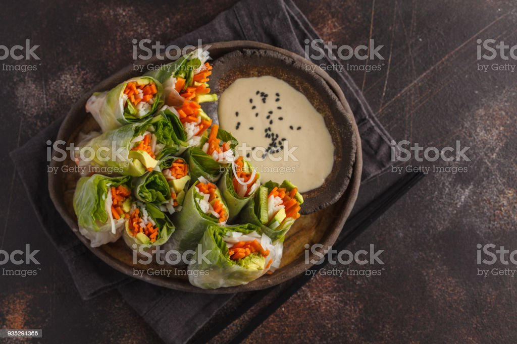 Fresh handmade vegan asian spring rolls with rice noodles, avocado, carrots and tahini dressing on black dish, dark background. Top view, copy space. stock photo