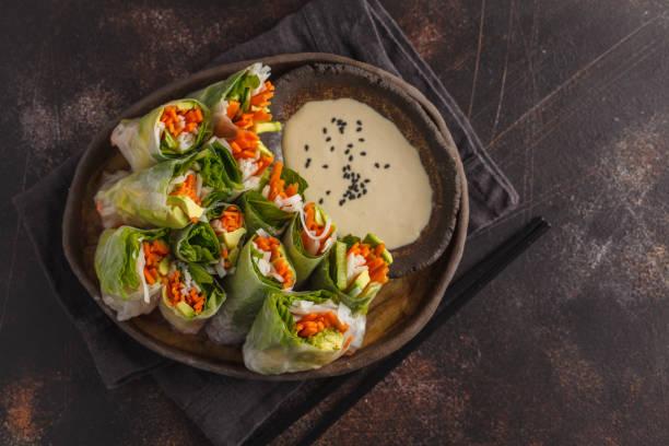 frische handgemachte vegane frühlingsrollen asiatische mit reisnudeln, avocado, karotten und tahini-dressing auf schwarzem teller, dunklen hintergrund. ansicht von oben, raum zu kopieren. - veggie wraps stock-fotos und bilder
