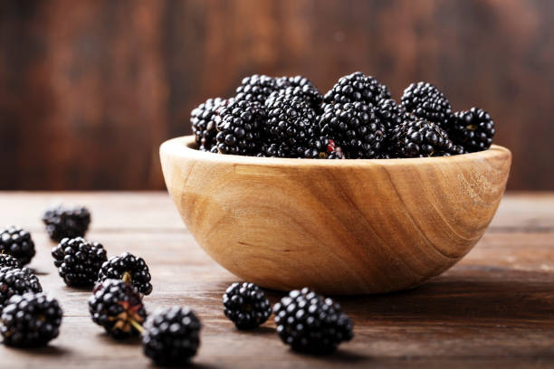 Fresh Harvest Blackberry Blackberry on a wooden background blackberry fruit stock pictures, royalty-free photos & images
