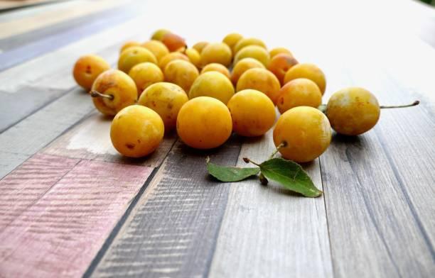 frisch geernteten gelben mirabellen auf holzboden - mirabellen stock-fotos und bilder