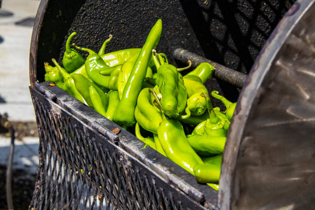 fresh hatch chilis in an outdoor barrel roaster getting ready to be cooked - green chilli pepper stock photos and pictures