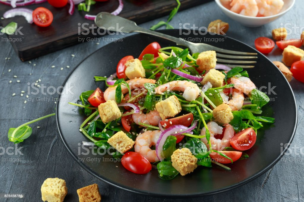 Fresh Healthy Prawns salad with tomatoes, red onion on black plate. concept healthy food stock photo