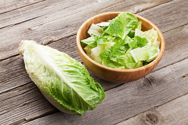 Fresh healthy romaine lettuce salad Fresh healthy romaine lettuce salad on wooden table romaine lettuce stock pictures, royalty-free photos & images